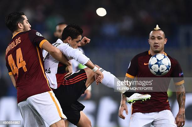 Leverkusen's Mexican forward Javier Hernandez fights for the ball with Roma's defender from Greece Kostas Manolas and Roma's midfielder from Belgium...