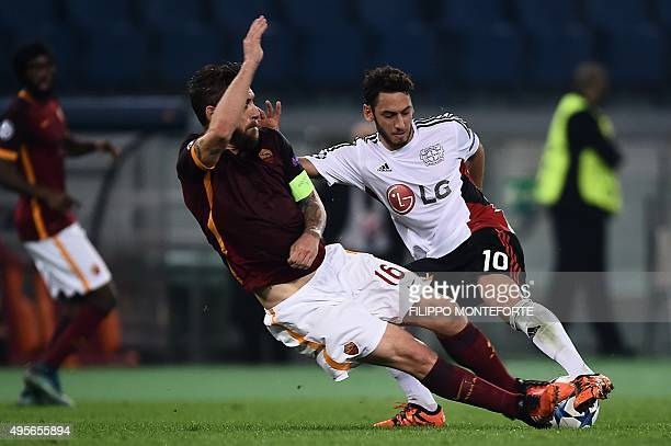 Leverkusen's midfielder Hakan Calhanoglu fights for the ball with Roma's midfielder from Italy Daniele De Rossi during the UEFA Champions League...