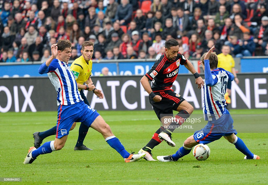 Leverkusen's midfielder Karim Bellarabi (C), Hertha's midfielder Niklas Stark and Hertha's defender Sebastian Langkamp(R) vie for the ball during the German first division Bundesliga football match Bayer 04 Leverkusen v Hertha Berlin in Leverkusen, western Germany, on April 30, 2016. / AFP / Roberto Pfeil