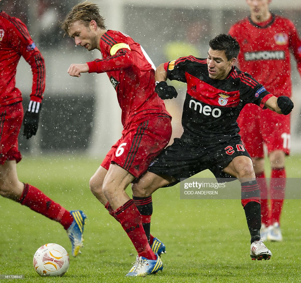 Leverkusen's midfielder Simon Rolfes (L) and Benfica's Argentinian forward Nicolas Gaitan vie for the ball during the UEFA Europa League football match Bayer 04 Leverkusen vs SL Benfica on February 14, 2013 in Leverkusen, western Germany. Benfica won the match 0-1.