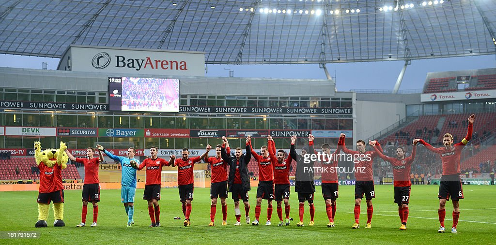Leverkusen's players celebrate with their mascot Brian the Lion (L) after the German first division Bundesliga football match Bayer Leverkusen vs FC Augsburg in Leverkusen, western Germany, on February 16, 2013. Leverkusen won the match 2-1. AFP PHOTO / PATRIK STOLLARZ