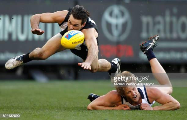 Levi Greenwood of the Magpies and Rory Sloane of the Crows compete for the ball during the 2017 AFL round 19 match between the Collingwood Magpies...