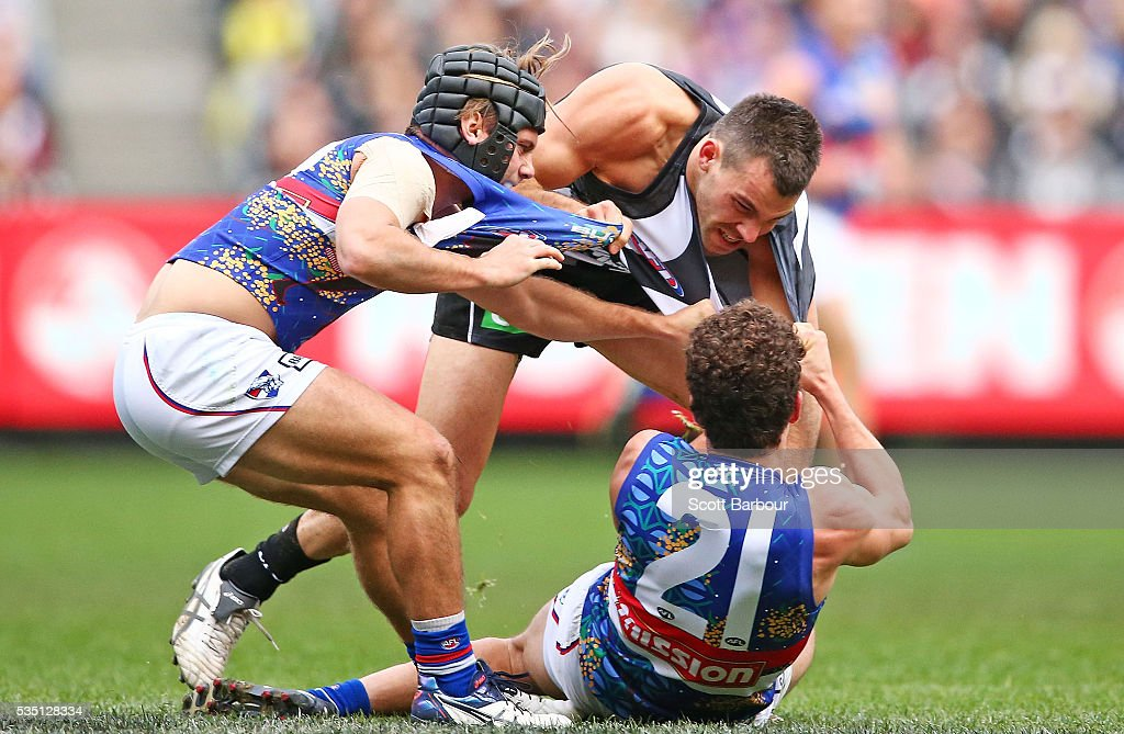 Levi Greenwood of the Magpies, Tom Liberatore of the Bulldogs and Caleb Daniel of the Bulldogs wrestle during the round 10 AFL match between the Collingwood Magpies and the Western Bulldogs at Melbourne Cricket Ground on May 29, 2016 in Melbourne, Australia.