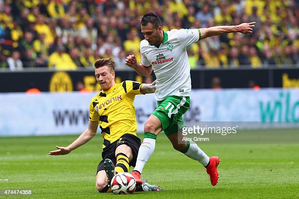 Levin Oeztunali of Bremen is challenged by Marco Reus of Dortmund during the Bundesliga match between Borussia Dortmund and Werder Bremen at Signal...