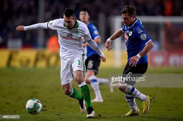 Levin Oeztunali of Bremen is challenged by Tom Schuetz of Arminia Bielefeld during the round of 16 DFB Cup match between Arminia Bielefeld and Werder...