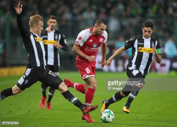 Levin Oeztunali of FSV Mainz 05 and Oscar Wendt of Borussia Moenchengladbach and Lars Stindl of Borussia Moenchengladbach battle for the ball during...