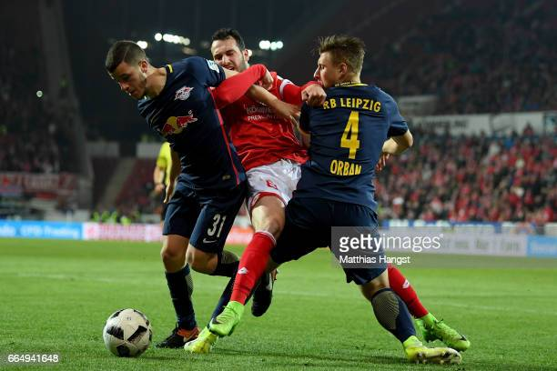Levin Oeztunali of Mainz and Diego Demme and Willi Orban of Leipzig battle for the ball during the Bundesliga match between 1 FSV Mainz 05 and RB...