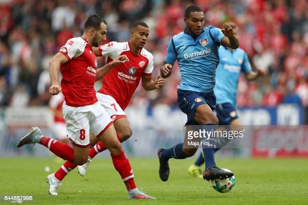 Levin Oeztunali of Mainz Robin Quaison of Mainz and Jonathan Tah of Bayer Leverkusen fight for the ball during the Bundesliga match between 1 FSV...