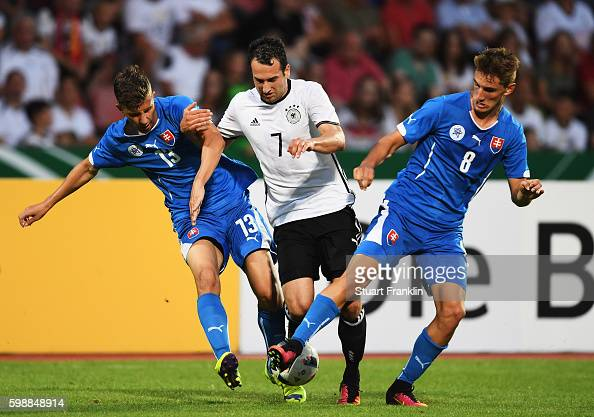 Levin ztunali of Germany is challenged by Martin Chrien and Lubomir Satka of Slovakia during the Under21 friendly match between U21 Germany and U21...