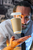 Levitating in the air paper cup with hot coffee and evaporation from it. Barista, a bearded young man in a white shirt with a tie, creates miracles - advertises his drink, causing it to soar