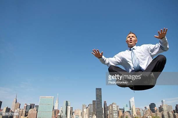Levitating Businessman Floating Above City Skyline