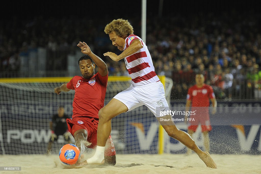 Lewie Valentine of USA is tackled by Patrick Tepa of Tahiti during the FIFA Beach Soccer World Cup Tahiti 2013 Group A match between USA and Tahiti at the Tahua To'ata stadium on September 21, 2013 in Papeete, French Polynesia.