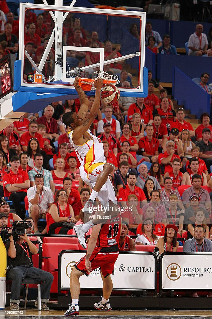 Lewis Bennie of the Tigers dunks and hangs during the round 14 NBL match between the Perth Wildcats and the Melbourne Tigers at Perth Arena on January 13, 2013 in Perth, Australia.