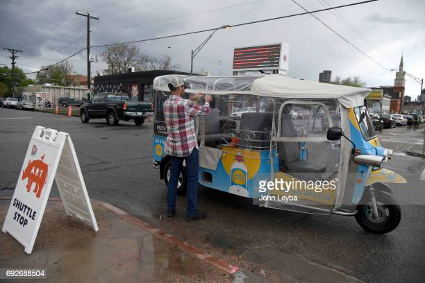 Lewis Davis General Manager ETUK zips up the rain canopy on his ETUK on June 2 2017 in Denver Colorado as he prepares to pick up customers to give a...