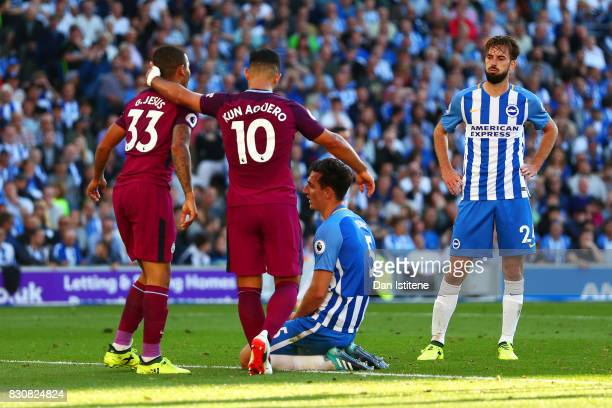 Lewis Dunk of Brighton and Hove Albion shows his dejection after scoring an own goal as Sergio Aguero and Gabriel Jesus of Manchester City celebrate...