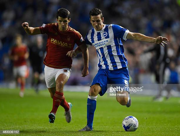 Lewis Dunk of Brighton is challenged by Eric Lichaj of Nottingham Forest during the Sky Bet Championship match between Brighton Hove Albion and...