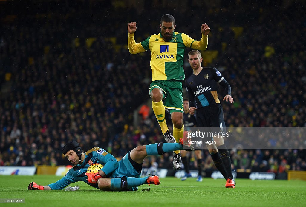 Lewis Grabban of Norwich City jumps over goalkeeper Petr Cech of Arsenal during the Barclays Premier League match between Norwich City and Arsenal at Carrow Road on November 29, 2015 in Norwich, England.