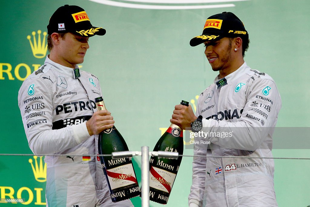 Lewis Hamilton and Nico Rosberg of Mercedes GP celebrate on the podium following the Japanese Formula One Grand Prix at Suzuka Circuit on October 5...