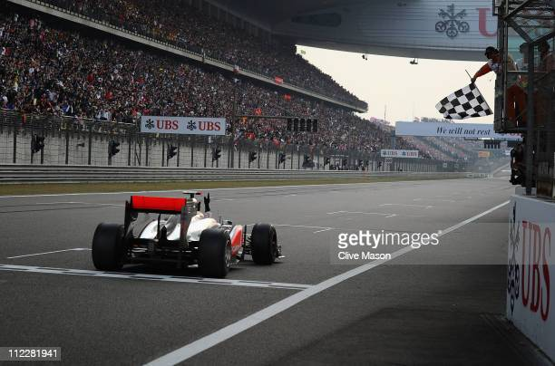 Lewis Hamilton of Great Britain and McLaren crosses the finishing line to win the Chinese Formula One Grand Prix at the Shanghai International...
