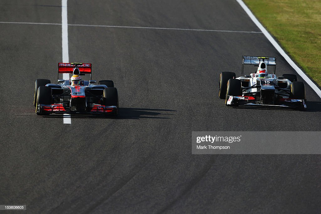 Lewis Hamilton of Great Britain and McLaren drives side by side with Sergio Perez of Mexico and Sauber F1 during the Japanese Formula One Grand Prix at the Suzuka Circuit on October 7, 2012 in Suzuka, Japan.