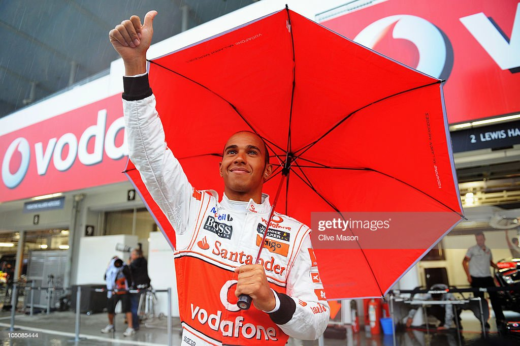 Lewis Hamilton of Great Britain and McLaren Mercedes waves to the crowd from outside his team garage as torrential rain causes the postponement of qualifying for the Japanese Formula One Grand Prix at Suzuka Circuit on October 9, 2010 in Suzuka, Japan.
