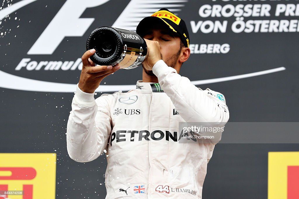 Lewis Hamilton of Great Britain and Mercedees GP celebrates his win on the podium during the Formula One Grand Prix of Austria at Red Bull Ring on...