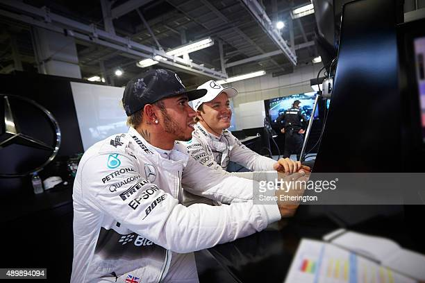 Lewis Hamilton of Great Britain and Mercedes GP and Nico Rosberg of Germany and Mercedes GP sit together in the garage during practice for the...
