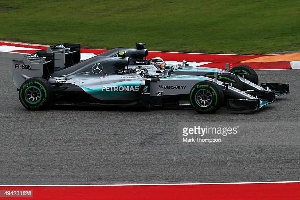 Lewis Hamilton of Great Britain and Mercedes GP and Nico Rosberg of Germany and Mercedes GP drive side by side through the first corner during the...