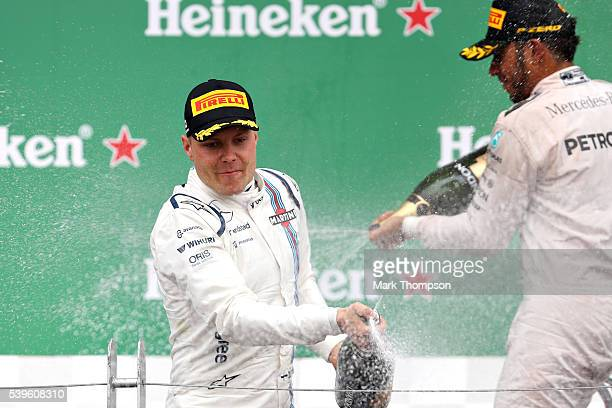 Lewis Hamilton of Great Britain and Mercedes GP and Valtteri Bottas of Finland and Williams celebrate on the podium during the Canadian Formula One...