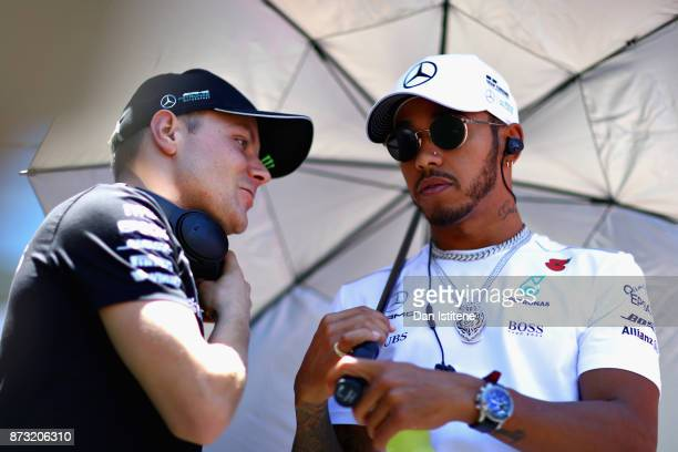 Lewis Hamilton of Great Britain and Mercedes GP and Valtteri Bottas of Finland and Mercedes GP talk on the drivers parade before the Formula One...