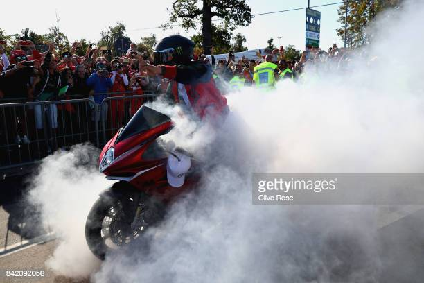 Lewis Hamilton of Great Britain and Mercedes GP arrives at the circuit and performs a burn out on his motorbike in front of fans before the Formula...
