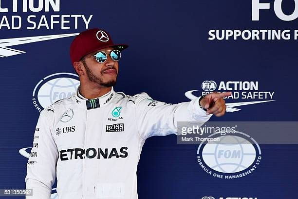 Lewis Hamilton of Great Britain and Mercedes GP celebrates after getting pole position in parc ferme during qualifying for the Spanish Formula One...