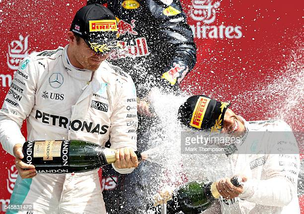 Lewis Hamilton of Great Britain and Mercedes GP celebrates his win on the podium with Nico Rosberg of Germany and Mercedes GP during the Formula One...
