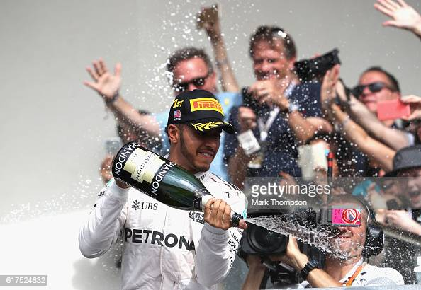 Lewis Hamilton of Great Britain and Mercedes GP celebrates his win on the podium during the United States Formula One Grand Prix at Circuit of The...