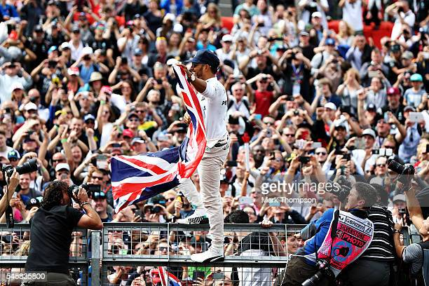 Lewis Hamilton of Great Britain and Mercedes GP celebrates his win with the fans on the pit wall during the Formula One Grand Prix of Great Britain...