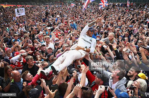 Lewis Hamilton of Great Britain and Mercedes GP celebrates his win with fans on the start finish straight after the Formula One Grand Prix of Great...