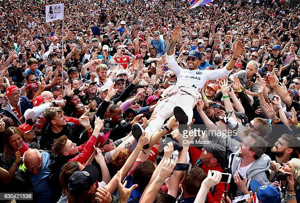 Lewis Hamilton of Great Britain and Mercedes GP celebrates his win with fans by crowd surfing on the start finish straight after the Formula One...