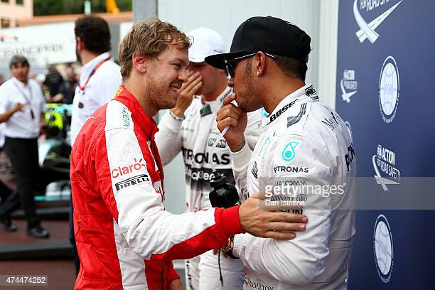 Lewis Hamilton of Great Britain and Mercedes GP celebrates in Parc Ferme with Sebastian Vettel of Germany and Ferrari after claiming pole position...