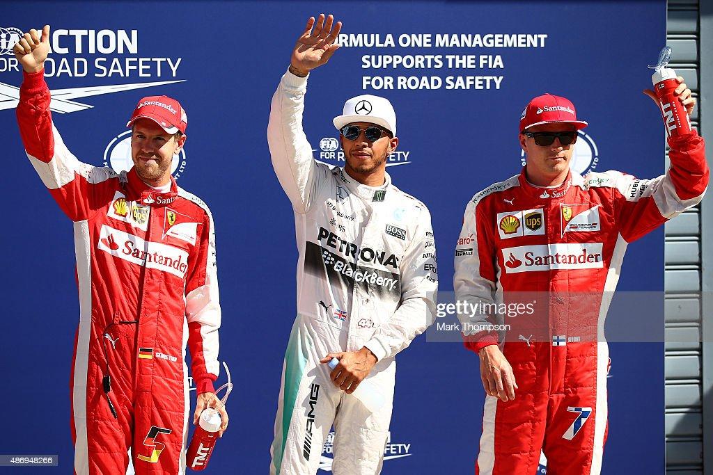 Lewis Hamilton of Great Britain and Mercedes GP celebrates in Parc Ferme next to Sebastian Vettel of Germany and Ferrari and Kimi Raikkonen of...