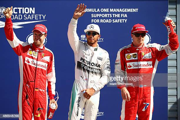 Lewis Hamilton of Great Britain and Mercedes GP celebrates in Parc Ferme next to Sebastian Vettel of Germany and Ferrari and Kimi Raikkonen of...