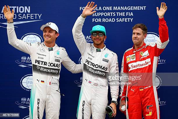 Lewis Hamilton of Great Britain and Mercedes GP celebrates next to Sebastian Vettel of Germany and Ferrari and Nico Rosberg of Germany and Mercedes...