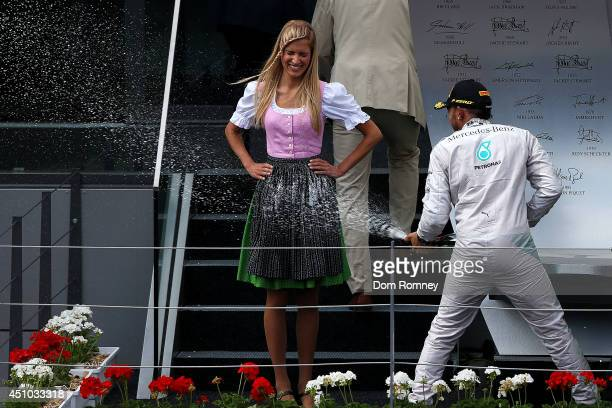 Lewis Hamilton of Great Britain and Mercedes GP celebrates on the podium after finishing second in the Austrian Formula One Grand Prix at Red Bull...