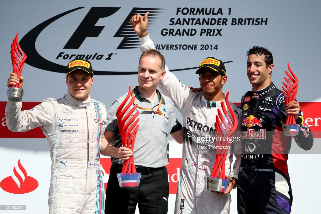 <a gi-track='captionPersonalityLinkClicked' href=/galleries/search?phrase=Lewis+Hamilton+-+Racecar+Driver&family=editorial&specificpeople=586983 ng-click='$event.stopPropagation()'>Lewis Hamilton</a> of Great Britain and Mercedes GP celebrates on the podium next to <a gi-track='captionPersonalityLinkClicked' href=/galleries/search?phrase=Valtteri+Bottas&family=editorial&specificpeople=8640136 ng-click='$event.stopPropagation()'>Valtteri Bottas</a> of Finland and Williams and <a gi-track='captionPersonalityLinkClicked' href=/galleries/search?phrase=Daniel+Ricciardo&family=editorial&specificpeople=6547569 ng-click='$event.stopPropagation()'>Daniel Ricciardo</a> of Australia and Infiniti Red Bull Racing after winning the British Formula One Grand Prix at Silverstone Circuit on July 6, 2014 in Northampton, United Kingdom.