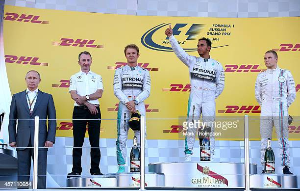 Lewis Hamilton of Great Britain and Mercedes GP celebrates on the podium next to Nico Rosberg of Germany and Mercedes GP Valtteri Bottas of Finland...