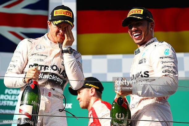 Lewis Hamilton of Great Britain and Mercedes GP celebrates on the podium next to Nico Rosberg of Germany and Mercedes GP after winning the Australian...