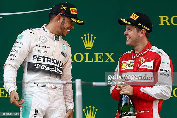 Lewis Hamilton of Great Britain and Mercedes GP celebrates on the podium with Sebastian Vettel of Germany and Ferrari after winning the Formula One...