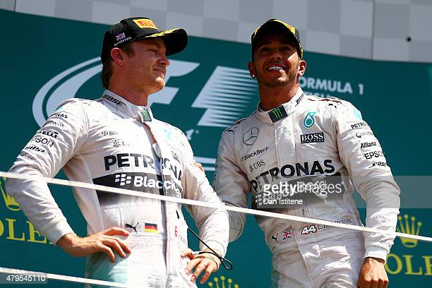 Lewis Hamilton of Great Britain and Mercedes GP celebrates on the podium next to Nico Rosberg of Germany and Mercedes GP after winning the Formula...
