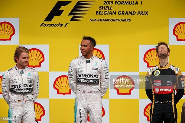 Lewis Hamilton of Great Britain and Mercedes GP celebrates on the podium next to Nico Rosberg of Germany and Mercedes GP and Romain Grosjean of...