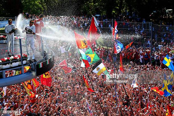 Lewis Hamilton of Great Britain and Mercedes GP celebrates on the podium next to Sebastian Vettel of Germany and Ferrari and Felipe Massa of Brazil...