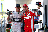 Lewis Hamilton of Great Britain and Mercedes GP celebrates on the podium next to Sebastian Vettel of Germany and Ferrari after winning the Formula...